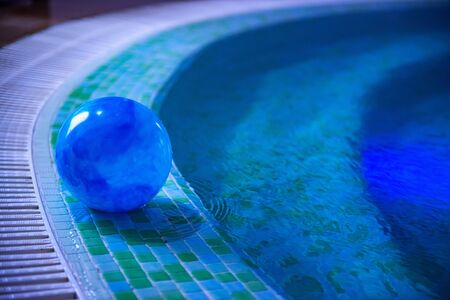 Blue ball is left in swimming pool decorated with blue and green mosaic tiles. Stairs are visible through shallow water. Summer season and private safety on water concepts. Selective focus. Copy space