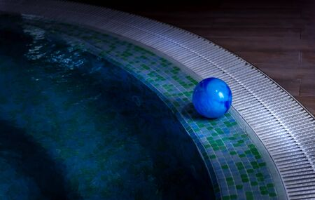 Blue ball is left on side of swimming pool decorated with mosaic tiles. Stairs are visible through shallow water. Summer season and private safety on water concepts. Selective focus. Copy space.