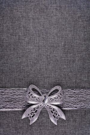Beautiful shiny tied silver glitter bow on silver colored ribbon and on gray natural textured burlap. Bow and ribbon are at the bottom of image. Vertical greeting card background. Large copy space.