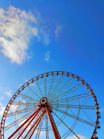 Partly visible bright red ferris wheel with red, green and yellow cabins. No people. Blue sky with soft white clouds. Vertical background with copy space. Summer leisure weekend concept.