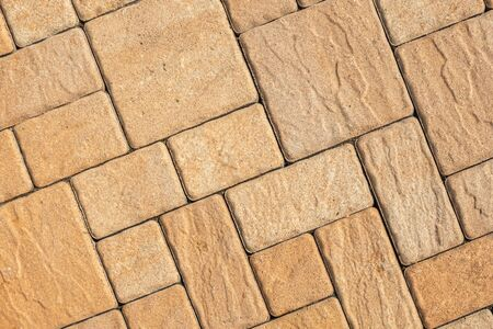 Highly detailed street pavement background with diagonal geometric pattern made of various square blocks with textured rough surface colored in beige or light brown. View from above. Copy space. Stok Fotoğraf