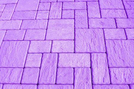 Geometric horizontal light purple background with pavement made of square blocks of different shapes and sizes. Perpendicular and parallel lines. Toned image, high angle view, copy space.