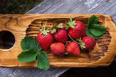 Few bright red organic strawberries on handmade wooden board and on old textured wooden surface. Unfocused real garden environment at background. Selective focus. Healthy eating and dieting concepts.