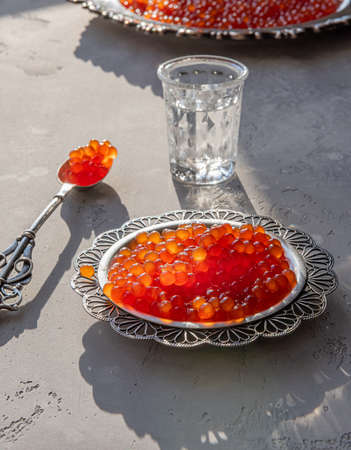 Red caviar in silver spoon and plate on gray background. Vodka shot and plate of caviar at unfocused background. Selective focus. Healthy eating concept. Russian style food background with copy space.