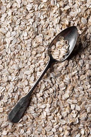Metal spoon with few flakes of rolled oats in it. Spoon is on layer of rolled oats. Source of vegetable protein. Healthy and sport eating concept background. Directly above view. Vertical orientation. Stock fotó