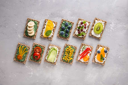 Set of homemade sandwiches with vegetables, fruits, berries, chlorella, spirulina and cheese. Kiwi, grape, banana, blueberry, peach, tangerine, pepper, tomato, corn, cucumber, mint, rosemary toppings.
