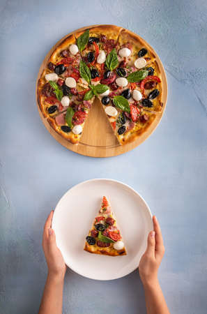 Italian pizza with ham, salami, black olives, white mozzarella cheese, red tomatoes and green basil leaves on blue textured table background. Two small hands are holding white plate with pizza slice.