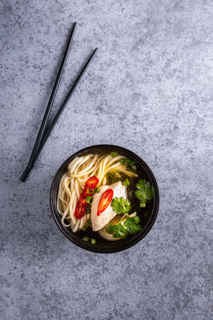Spicy asian soup. Chicken bouillon and meat, red chilli pepper, fresh cilantro and scallions, japanese noodles in black soup bowl with chopsticks on gray surface. Vertical orientation. Copy space.