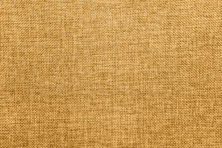 Empty abstract background with natural burlap detailed texture. Ecology friendly rough fabric threads toned in honey dijon mustard color. Copy space. Surface from directly above view. Stock Photo