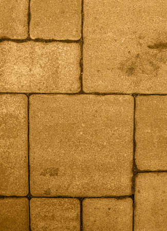Vertical background with geometric pattern of highly detailed street pavement made of various square blocks. Textured rough surface toned in honey dijon color. View from directly above. Copy space. Stok Fotoğraf