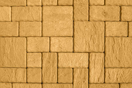 Highly detailed street pavement background with geometric pattern made of square blocks of different sizes with textured rough surface toned in honey dijon. View from directly above. Copy space.