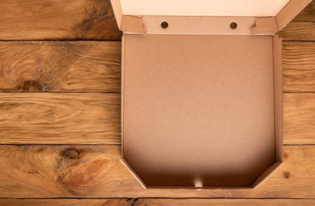 Part of new clean brown opened empty pizza box made of paperboard on natural wooden background. Horizontal orientation. View from above. Copy space. Mockup for home delivery and stay home concept.