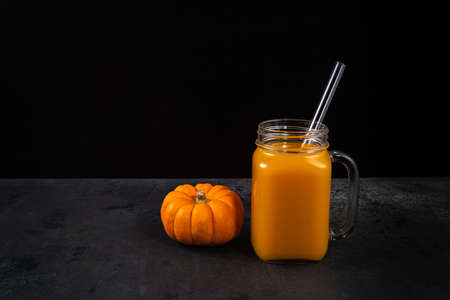 One square glass jar with non-alcoholic pumpkin mocktail and glass straw on black textured surface. Whole pumpkin is near jar. Horizontal background for Halloween with copy space. Selective focus. Archivio Fotografico
