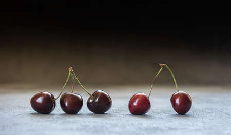 Close-up of dark red and black sweet cherries. Five sweet cherries in a row on brown and gray blue surface. Horizontal background with copy space. Healthy eating and dieting concept. Selective focus.
