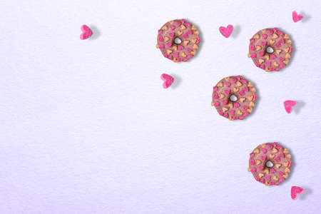 Three tasty glazed pink doughnuts with marshmallow hearts. Few hearts are flying around doughnuts. Textured lilac paper background. Template for Valentine greeting card with levitation. Copy space.