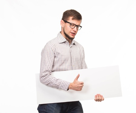 saxy: Young saxy man portrait of a confident businessman showing presentation, pointing paper placard gray background. Ideal for banners, registration forms, presentation, landings, presenting concept. Stock Photo