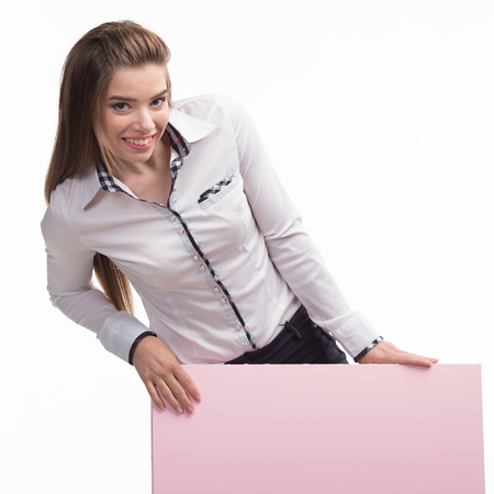 Young encouraged woman portrait of a confident businesswoman showing presentation, pointing placard pink background. Ideal for banners, registration forms, presentation, landings, presenting concept.. Stock Photo