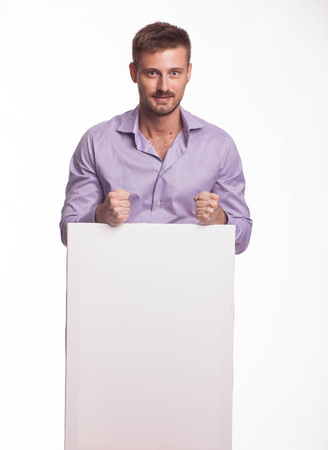Young encouraged man portrait of a confident businessman showing presentation, pointing placard gray background. Ideal for banners, registration forms, presentation, landings, presenting concept.