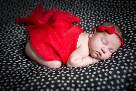 Sleeping pretty newborn in red dress and a small ribbon on his head.