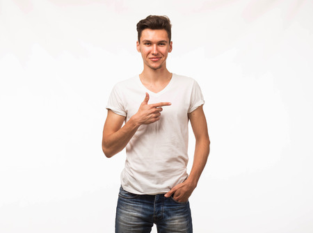 Young happy man portrait of a confident businessman showing by hands on a gray background. Ideal for banners, registration forms, presentation, landings, presenting concept.