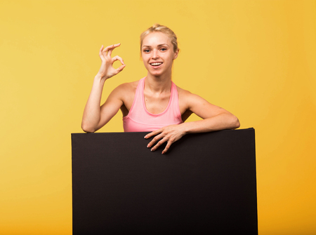 Young happy  portrait of a confident woman showing presentation, pointing placard yellow background. Ideal for banners, registration forms, presentation, landings, presenting concept. Standard-Bild