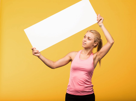 Young pry portrait of a confident woman showing presentation, pointing placard yellow background. Ideal for banners, registration forms, presentation, landings, presenting concept.