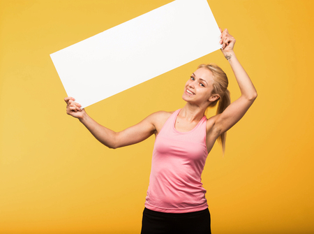Young happy portrait of a confident woman showing presentation, pointing placard yellow background. Ideal for banners, registration forms, presentation, landings, presenting concept.