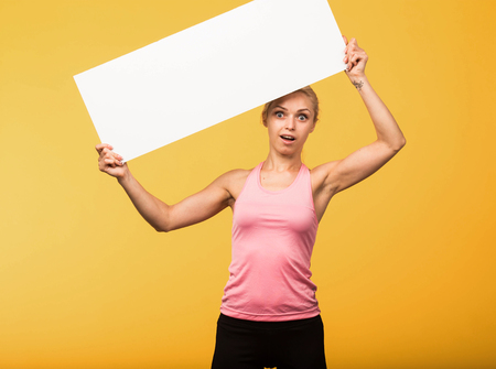 Young surprised portrait of a confident woman showing presentation, pointing placard yellow background. Ideal for banners, registration forms, presentation, landings, presenting concept.