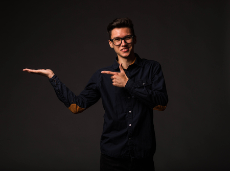 Young jocular man portrait of a confident businessman showing by hands on a black background. Ideal for banners, registration forms, presentation, landings, presenting concept. Standard-Bild