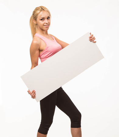 Young confident portrait of a woman showing presentation, pointing placard gray background. Ideal for banners, registration forms, presentation, landings, presenting concept. Standard-Bild