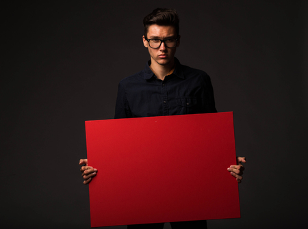 Young serious man portrait of a confident businessman showing presentation, pointing paper placard black background. Ideal for banners, registration forms, presentation, landings, presenting concept.