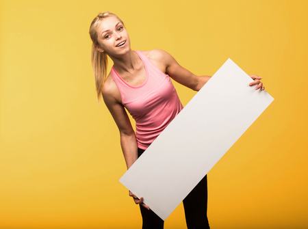 Young glad portrait of a confident woman showing presentation, pointing placard yellow background. Ideal for banners, registration forms, presentation, landings, presenting concept.