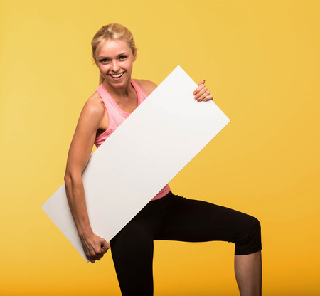 Young cheerful portrait of a confident woman showing presentation, pointing placard yellow background. Ideal for banners, registration forms, presentation, landings, presenting concept.
