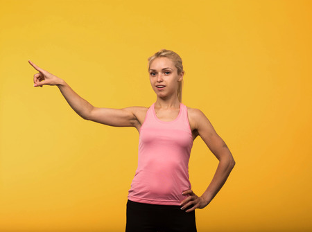 Young glad  portrait of a confident woman showing by hands on a yellow background. Ideal for banners, registration forms, presentation, landings, presenting concept Standard-Bild