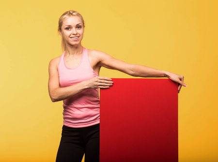 Young glad  portrait of a confident woman showing presentation, pointing placard yellow background. Ideal for banners, registration forms, presentation, landings, presenting concept. Standard-Bild