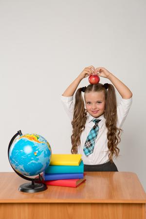 幸せな小さな女子高生彼女の頭の上の赤いリンゴと白い背景に立っている、白いブラウスを着てします。学校のコンセプトです。バナー、登録フォ