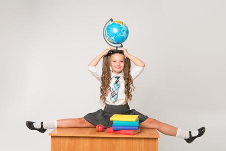 幸せな小さな女子高生彼女の頭の上のグローブ ホワイト バック グラウンドに立っている、白いブラウスを着てします。学校のコンセプトです。バ