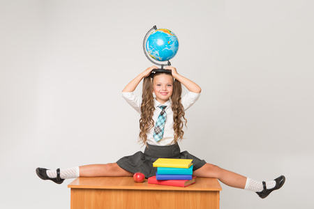 Happy little schoolgirl with globe on her head, wearing white blouse , standing against white background. Back to school concept. Ideal for banners, registration forms, presentation. Reklamní fotografie