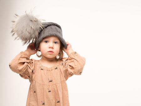 Portrait of pensive little girl. Cute little girl in beige dress in a gray hat isolated on white background. Standard-Bild