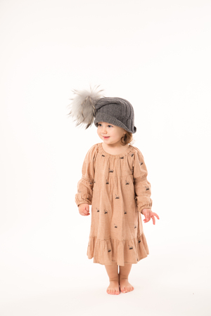 Portrait of happy little girl. Cute little girl in beige dress in a gray hat isolated on white background.