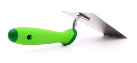 Metal trowel with a green plastik handly on a white background.