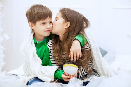 The little girl kisses and hugs boy. The concept of love and Valentines Day. Stock Photo