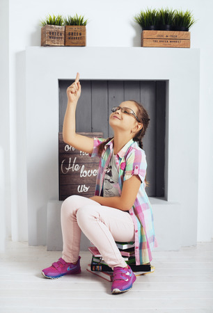 Prodigy: little girl in glasses sits on books. The concept of education and childhood.