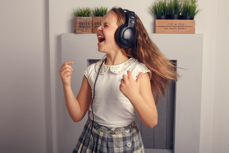 emotional child in headphones singing and dancing. The concept of lifestyle and music.