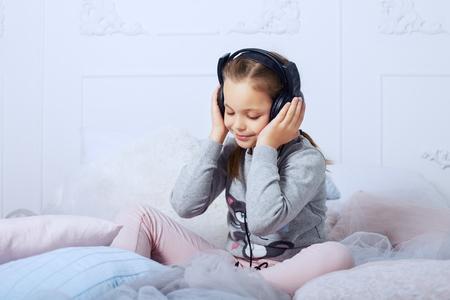 子供のベッドの上で座っていると、オーディオ ブックを聴く女子高生。幼年期、教育および音楽のコンセプトです。 写真素材