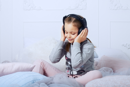 Child schoolgirl sitting on a bed and listening to an audiobook. The concept of childhood, education and music.