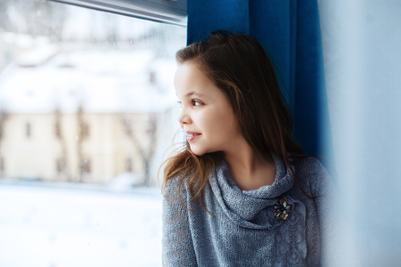 Little beautiful girl looking out the window. The concept of childhood and home. Stock Photo