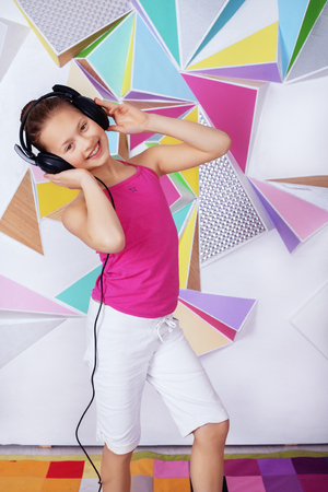 Funny child girl in headphones sings and dances. The concept of music and childhood.