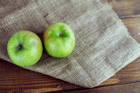 Two juicy green apples on the table. The concept of healthy eating and vegetarianism. Stock Photo