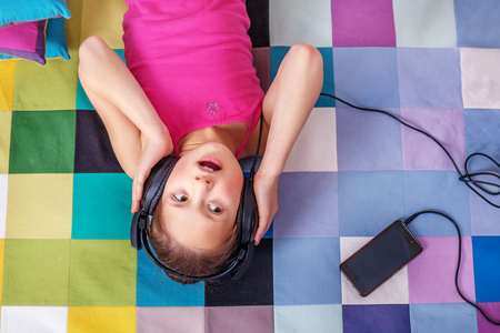 Child student listening to an audiobook on headphones.  The concept of learning, music, childhood.